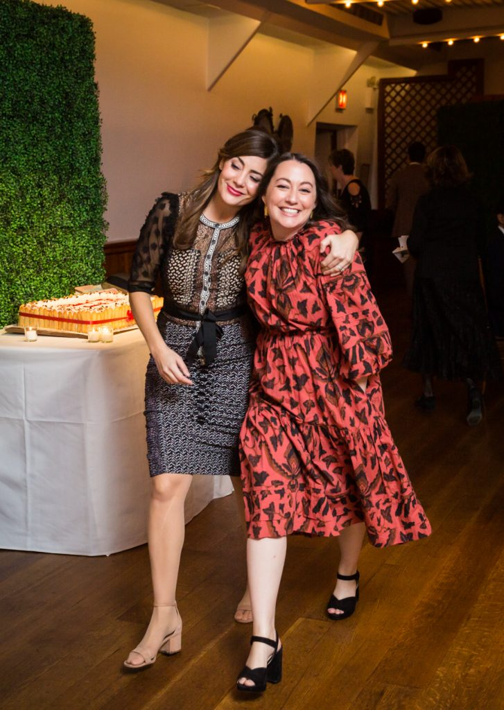 Two women walking together into a reception at a Water Club wedding
