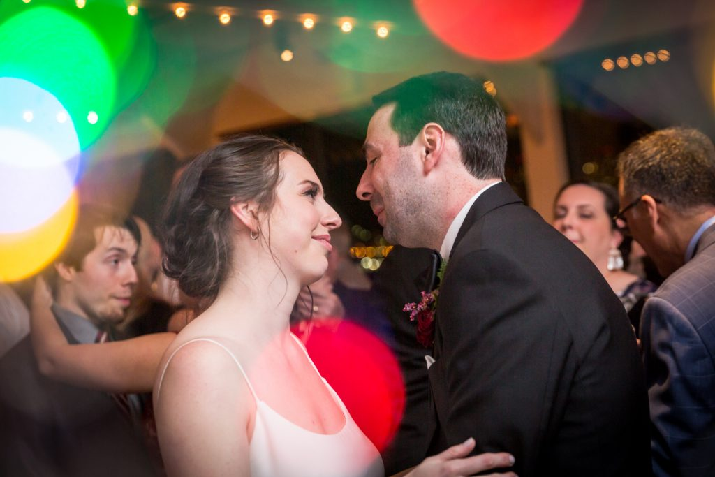Bride and groom dancing with colored lights surrounding at a Water Club wedding