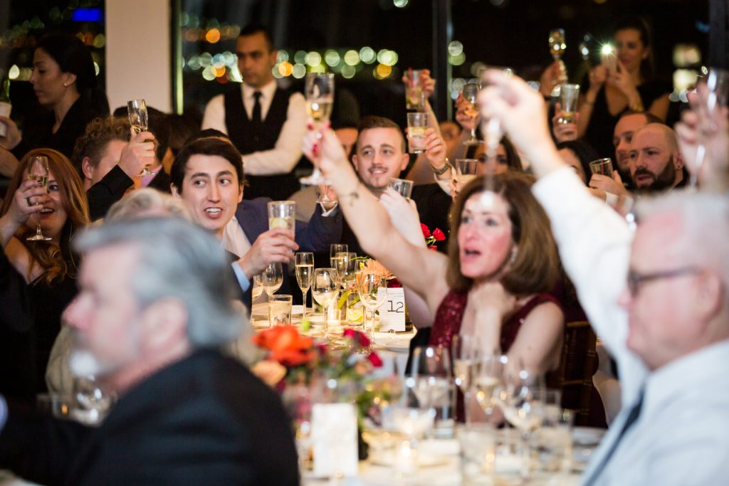 Guests toasting with raised glasses at a Water Club wedding