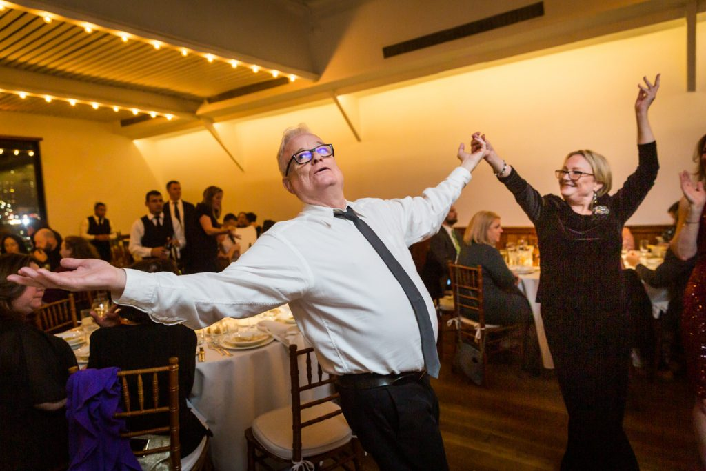 Older man and woman dancing with hands outstretched at a Water Club wedding