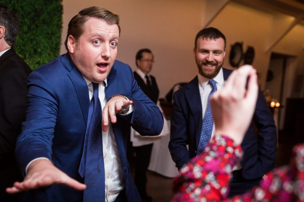 Man wearing blue blazer dancing with arms to the camera