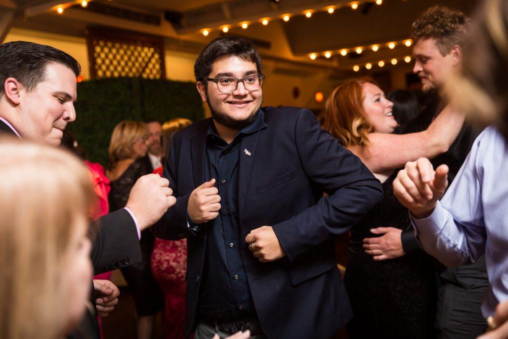 Man in black suit dancing on dance floor at a Water Club wedding