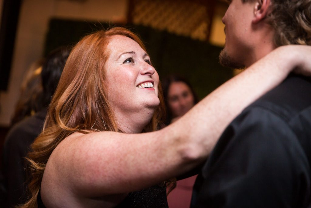 Red haired woman reaching to other guest at a Water Club wedding
