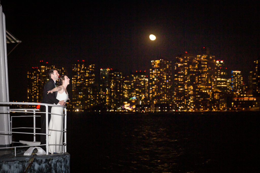 Bride and groom in Titanic pose with Queens skyline in background at a Water Club wedding