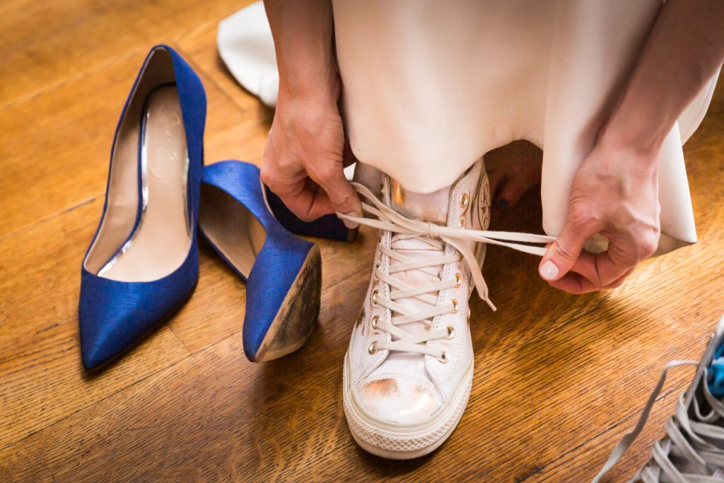 Close up of bride tying tennis shoe with blue heels to the left at a Water Club wedding