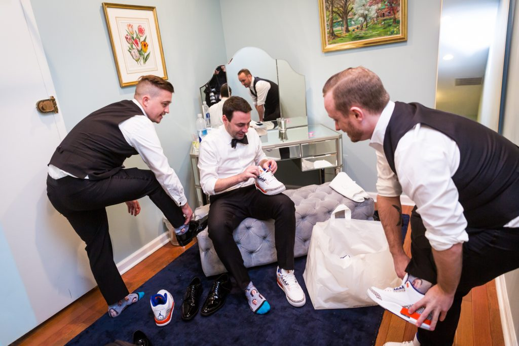 Groom and groomsmen changing into tennis shoes at a Water Club wedding