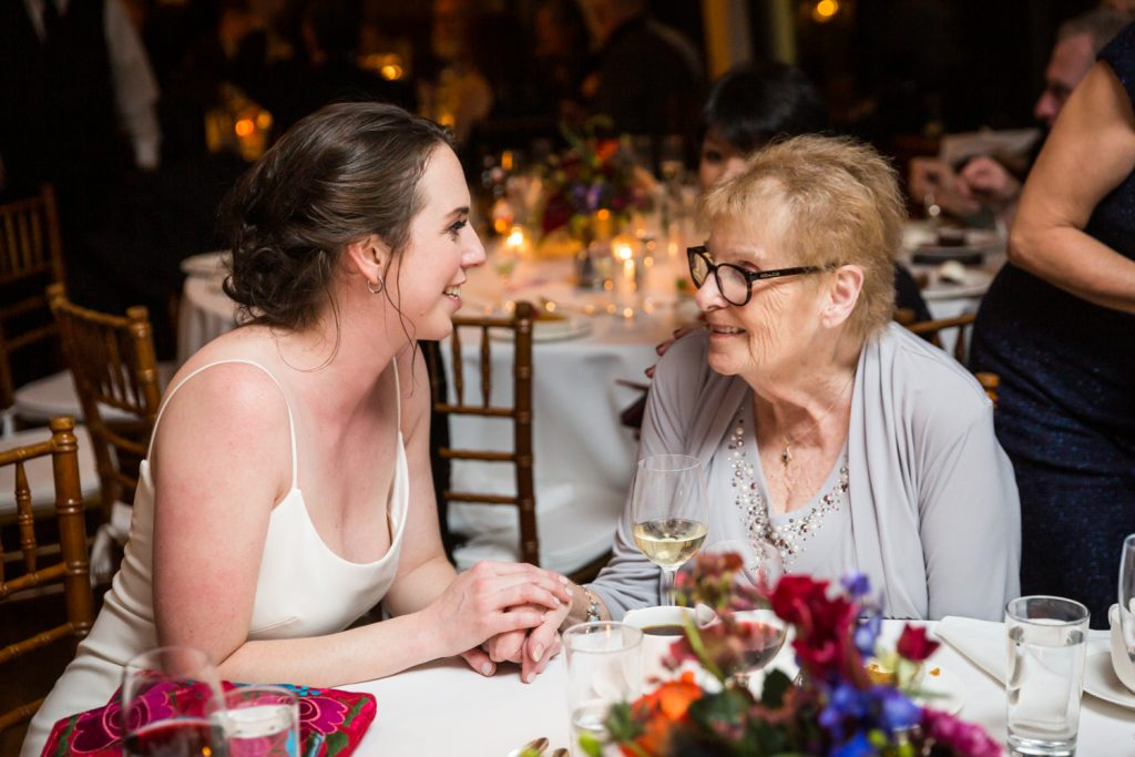 Bride holding hands with elderly guest at a Water Club wedding
