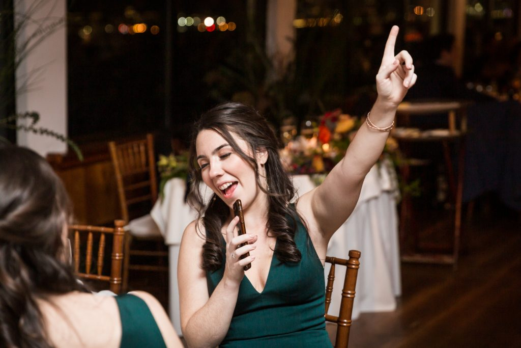 Bridesmaid singing into her cell phone at a Water Club wedding