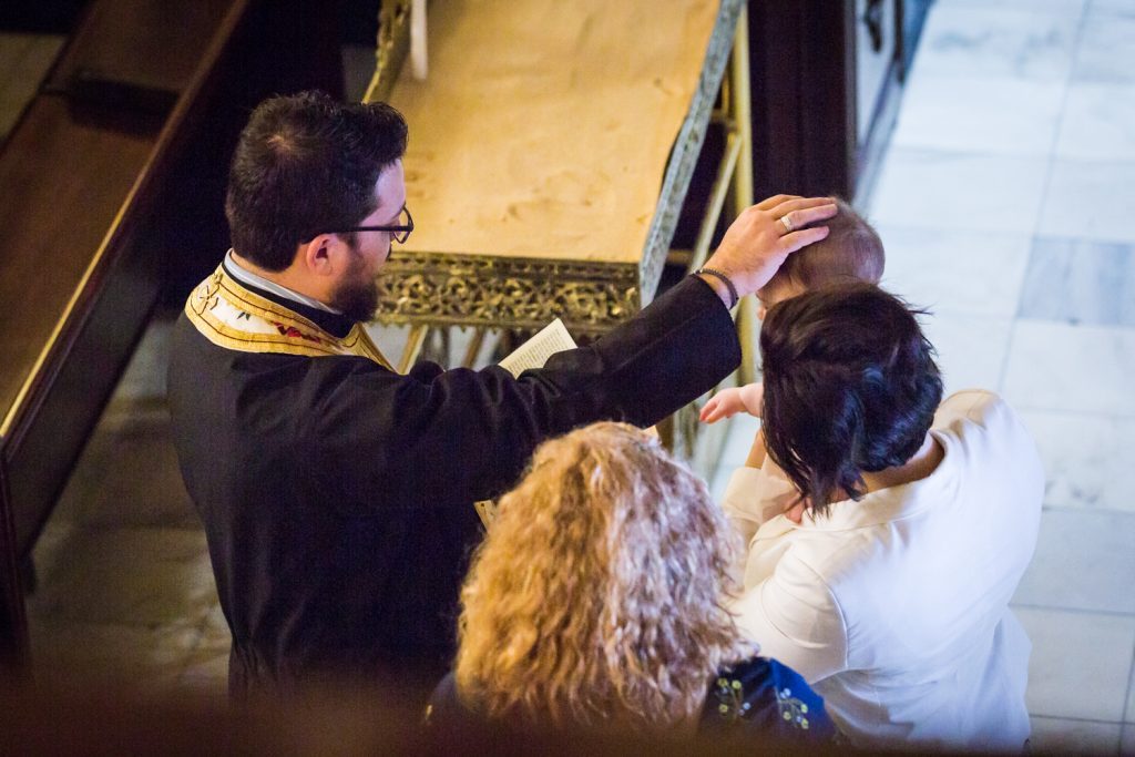Greek orthodox baptism photos of priest with hand on baby