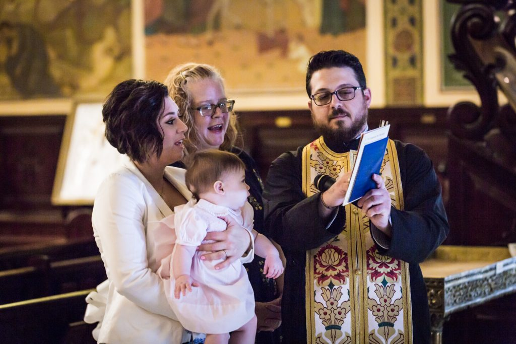 Greek orthodox baptism photos of priest reading to baby and godparents