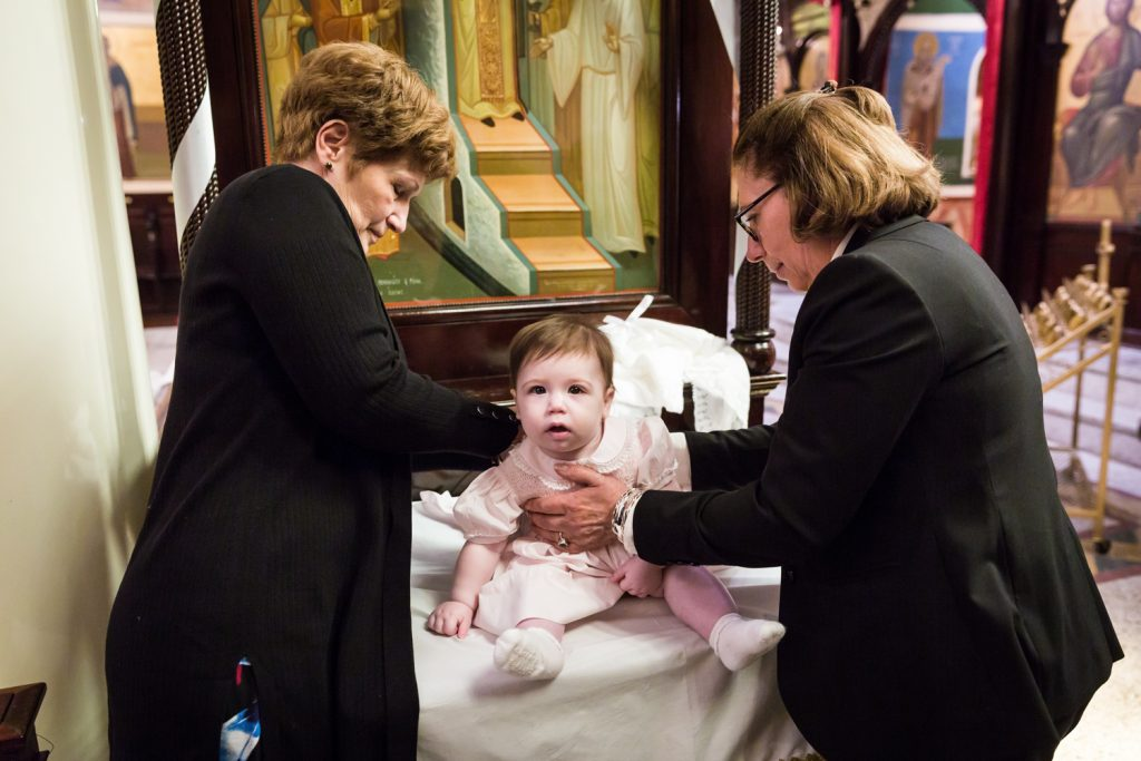 Greek orthodox baptism photos of godparents dressing baby