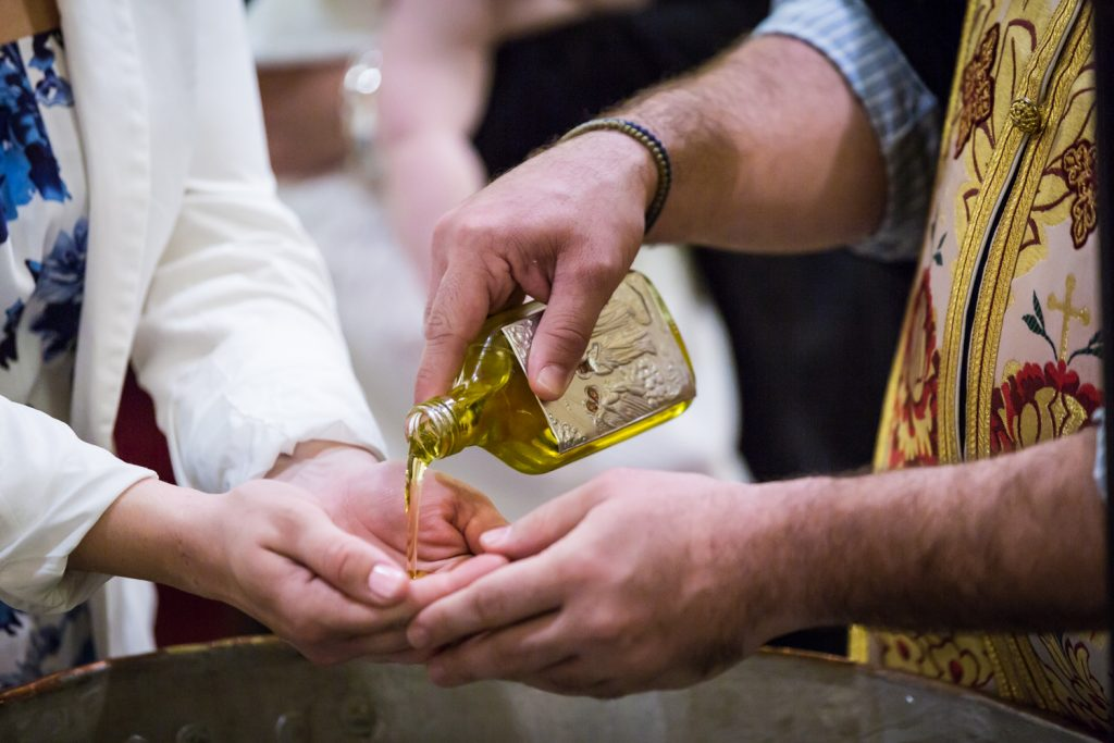 Close up of priest pouring oil into hands of godparent