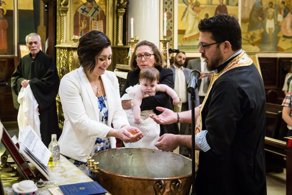 Greek orthodox baptism photos of priest pouring oil into hands of godmother
