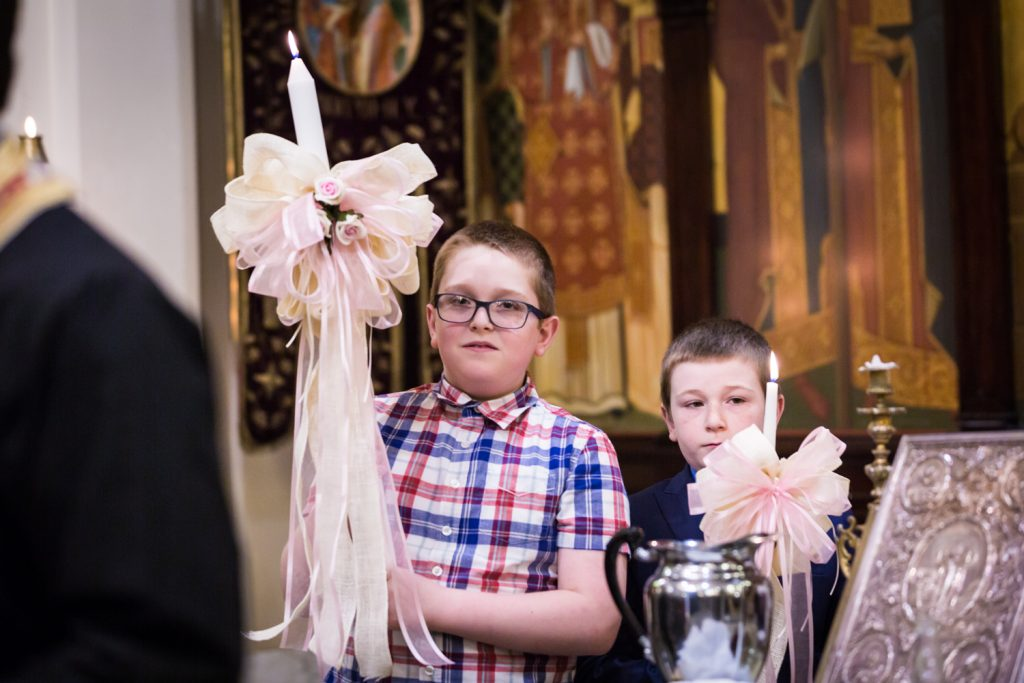 Greek orthodox baptism photos of two boys holding candles with bows
