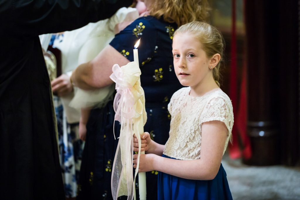 Greek orthodox baptism photos of young girl holding candle with bow