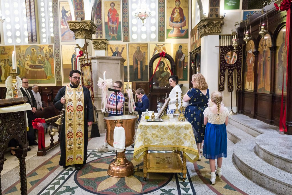 Greek orthodox baptism photos of priest and guests circling altar