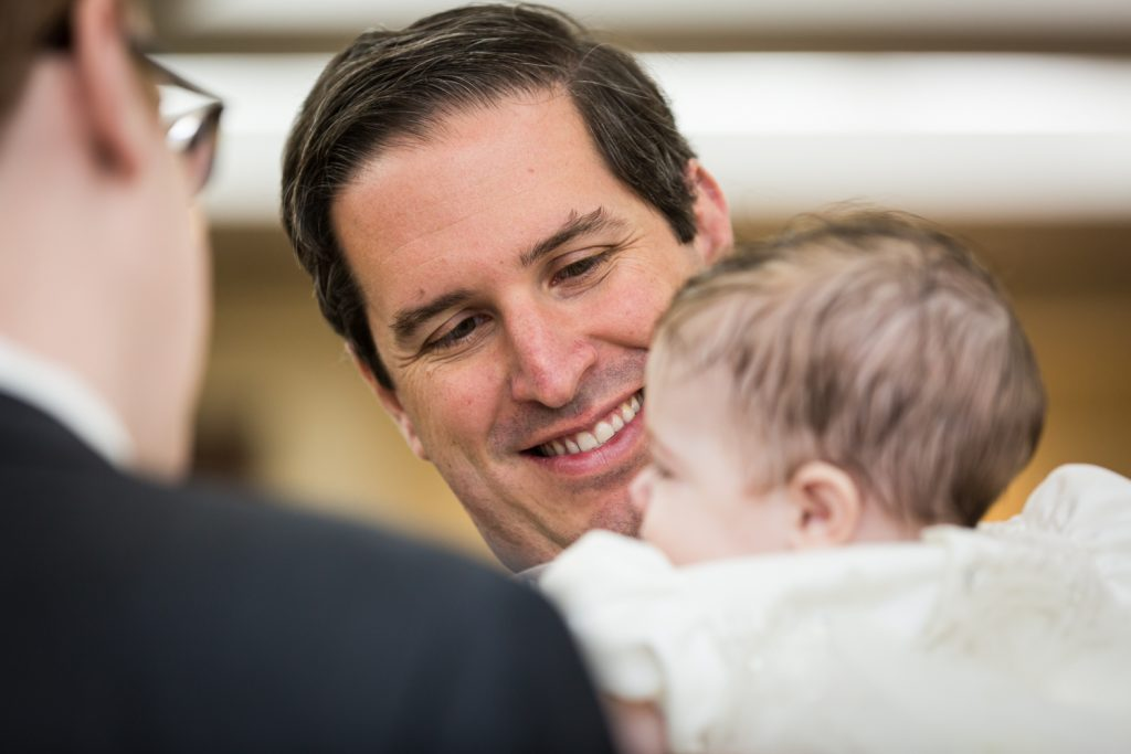 Man smiling at baby at Greek orthodox baptism reception