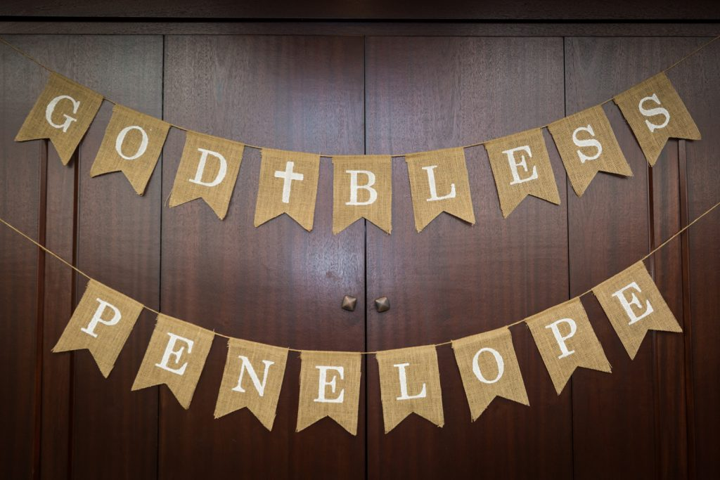Hanging sign at baptism that says 'God Bless Penelope'