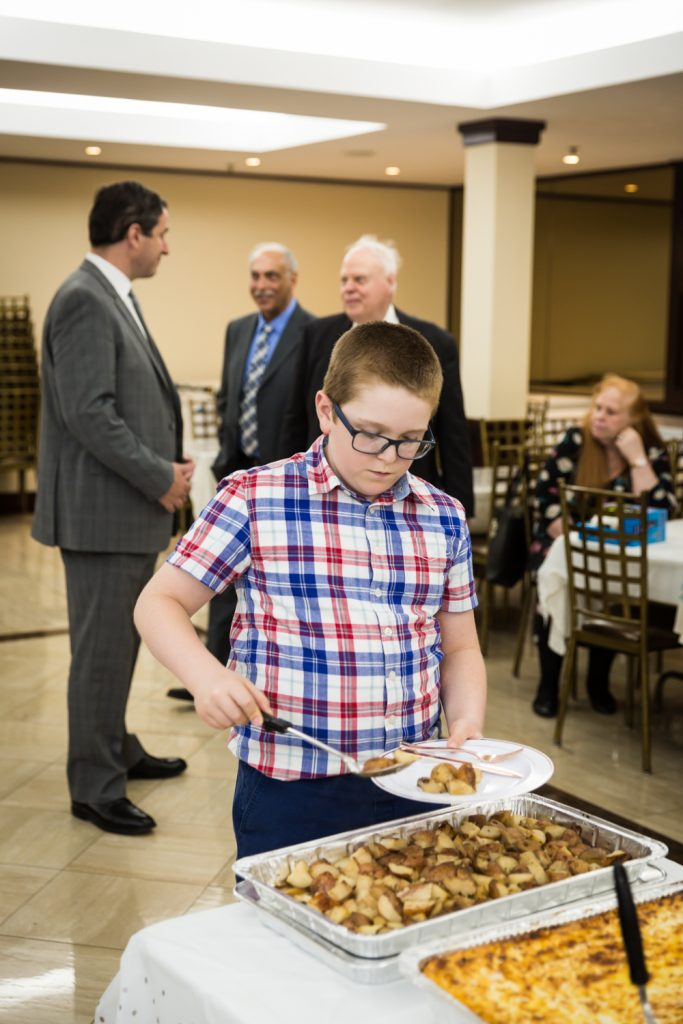 Boy putting food on his plate at Greek orthodox baptism reception