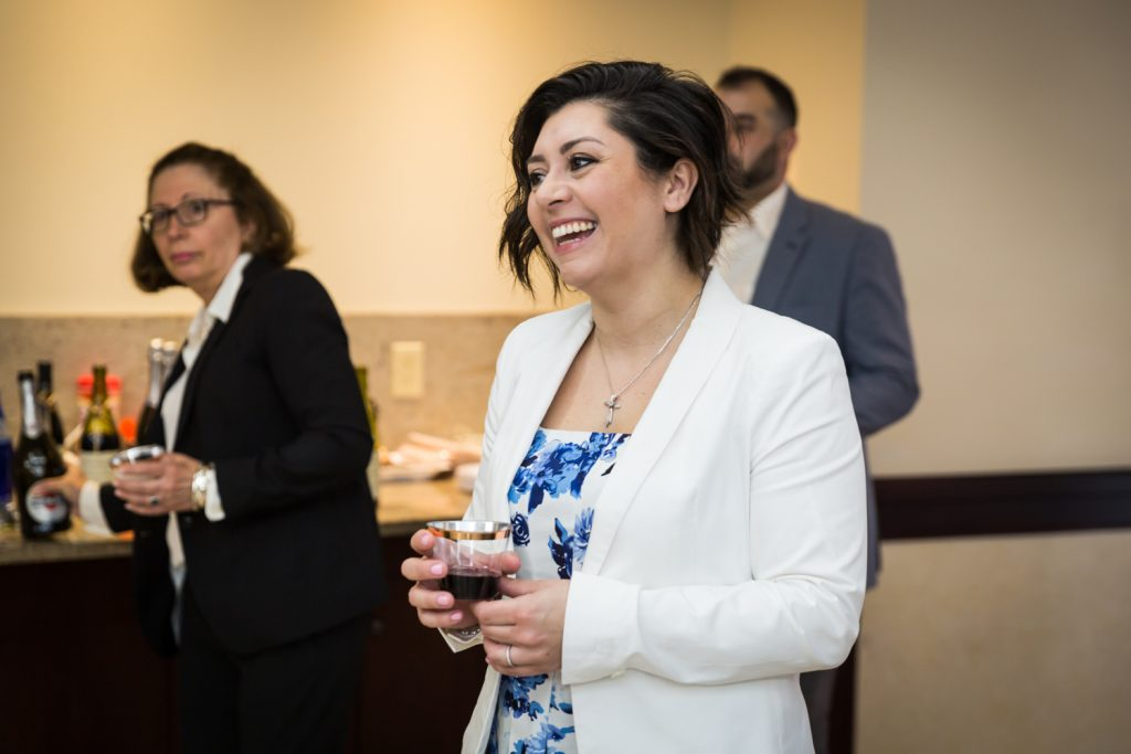 Woman wearing white jacket and holding glass of wine at Greek orthodox baptism reception