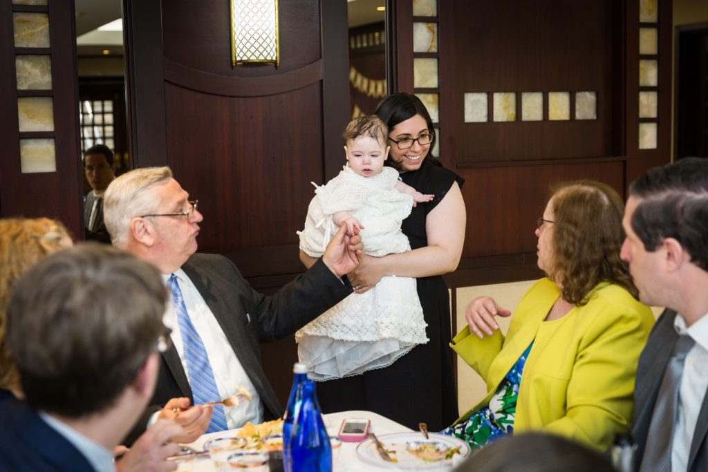 Mother showing off baby to table of guests at Greek orthodox baptism reception
