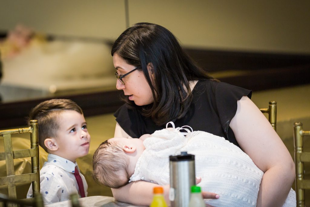 Mother holding baby and talking to little boy at Greek orthodox baptism reception