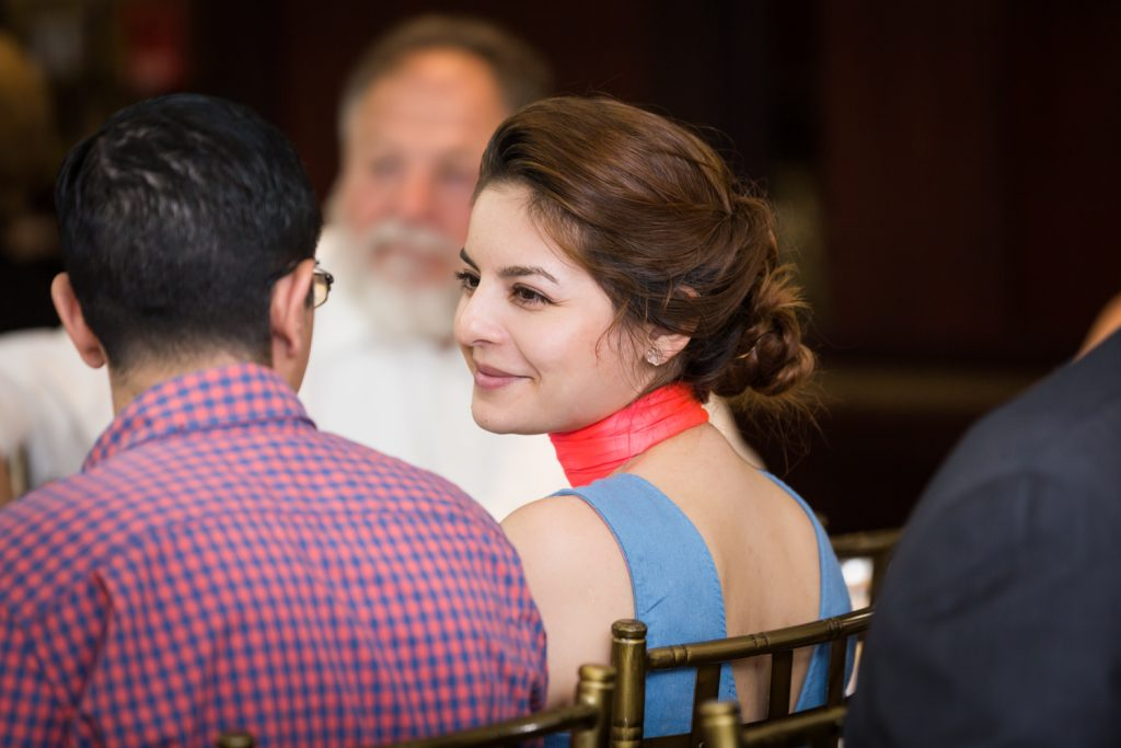 Female guest with hair in bun smiling at Greek orthodox baptism reception