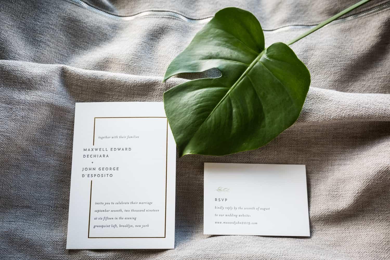 Wedding invitation and green leaf on grey pillow