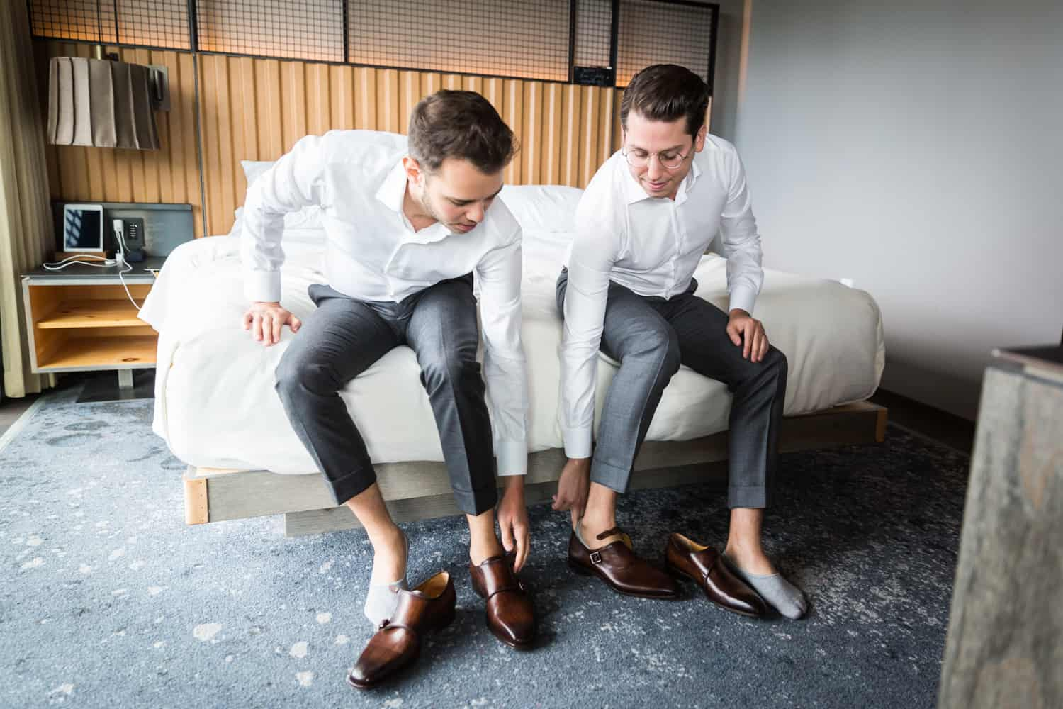 Greenpoint Loft wedding photos of two grooms putting on shoes while sitting on bed
