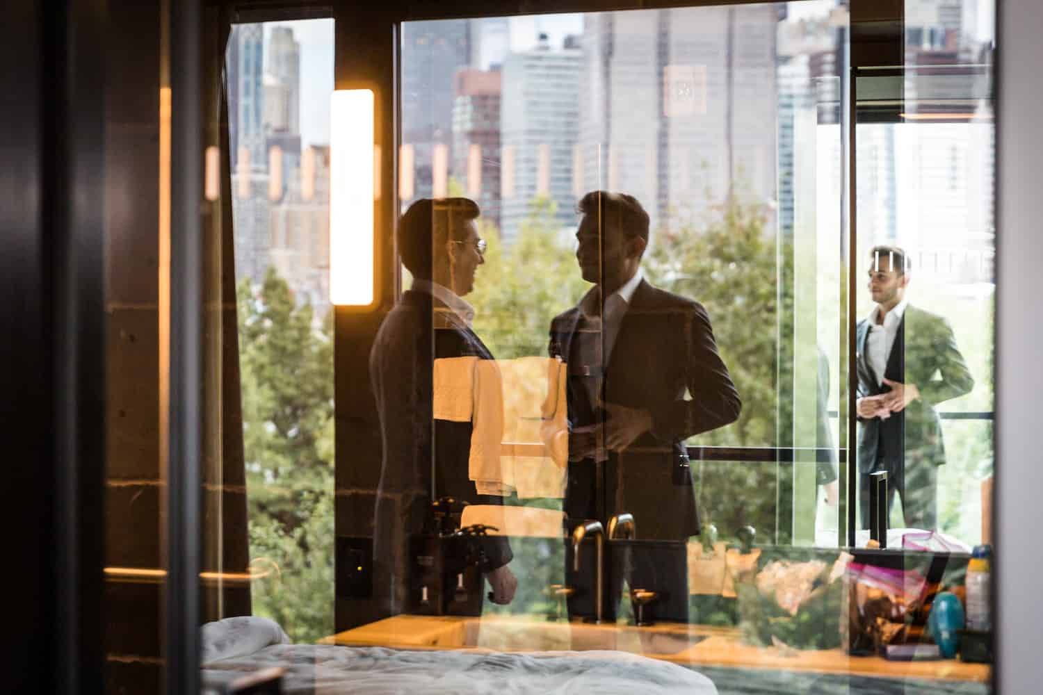 Reflection in glass of two grooms getting ready for their Greenpoint Loft wedding