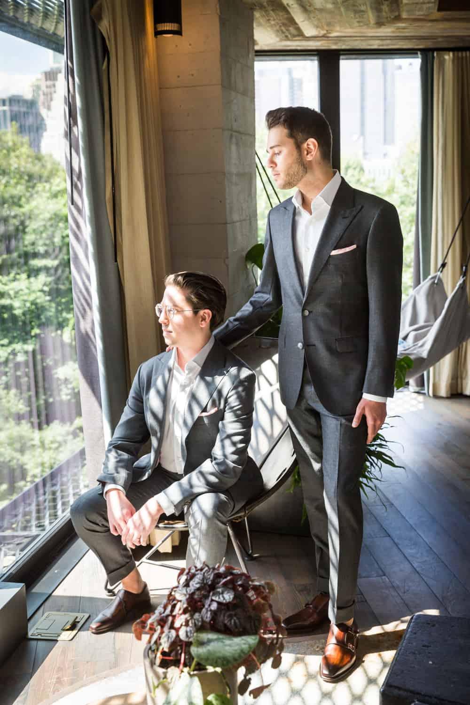 Greenpoint Loft wedding photos of one groom sitting and one groom standing near window