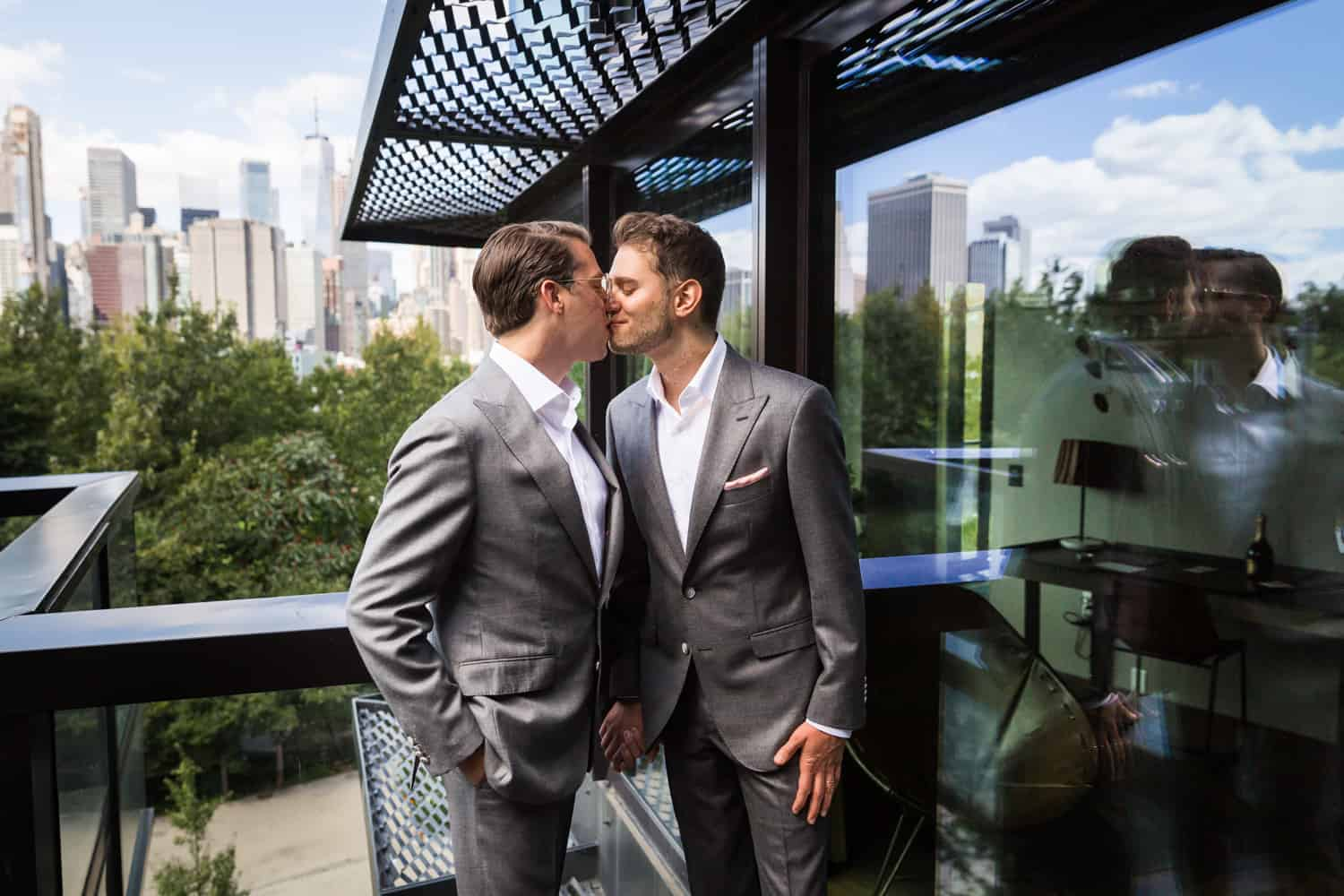 Greenpoint Loft wedding photos of two grooms kissing on hotel terrace
