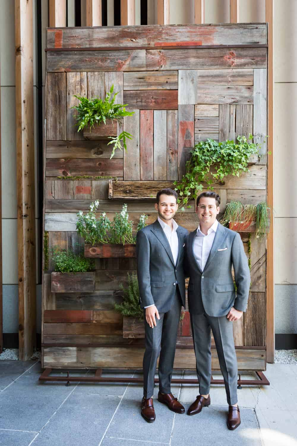 Greenpoint Loft wedding photos of two grooms in front of wall with plants