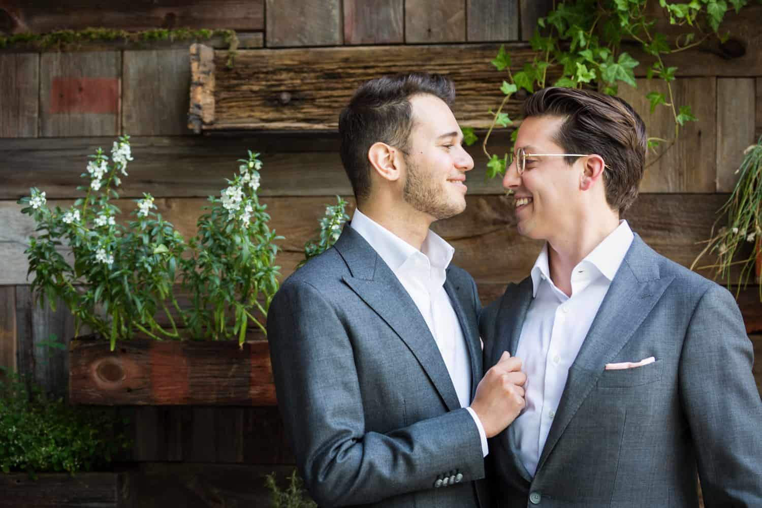 Greenpoint Loft wedding photos of two grooms in front of wooden wall with plants