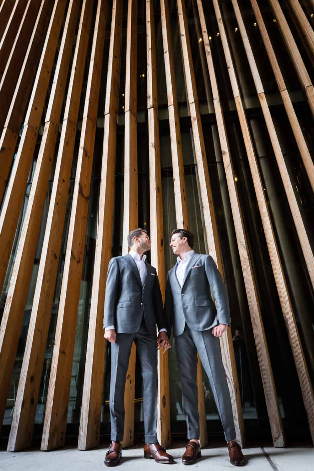 Greenpoint Loft wedding photos of two grooms standing in front of wall with wooden slats