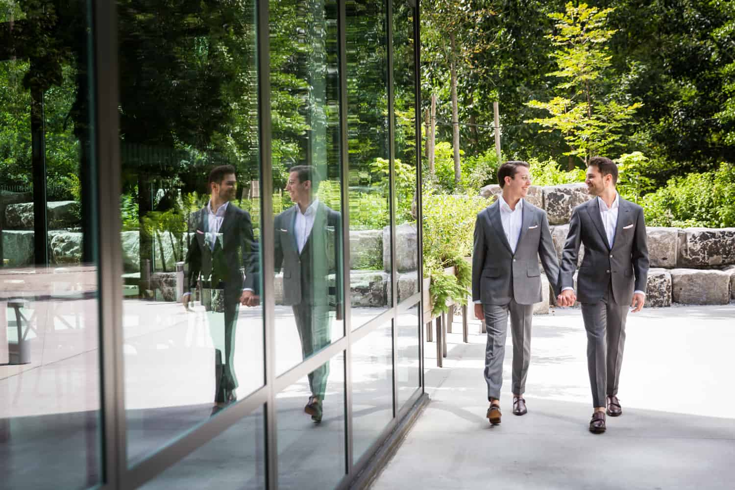 Greenpoint Loft wedding photos of two grooms walking hand-in-hand reflected in glass