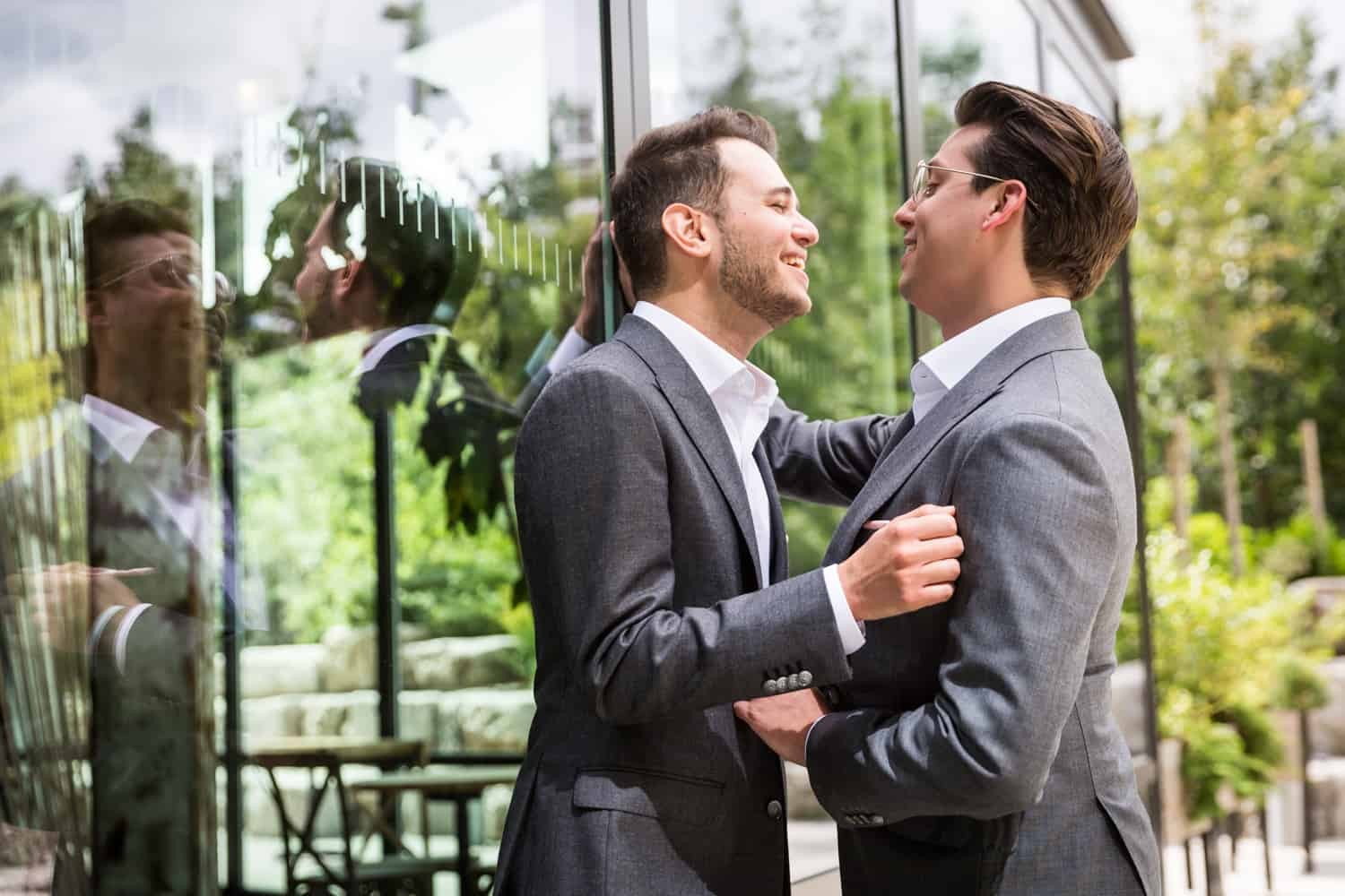 Greenpoint Loft wedding photos of two grooms leaning against glass wall and laughing