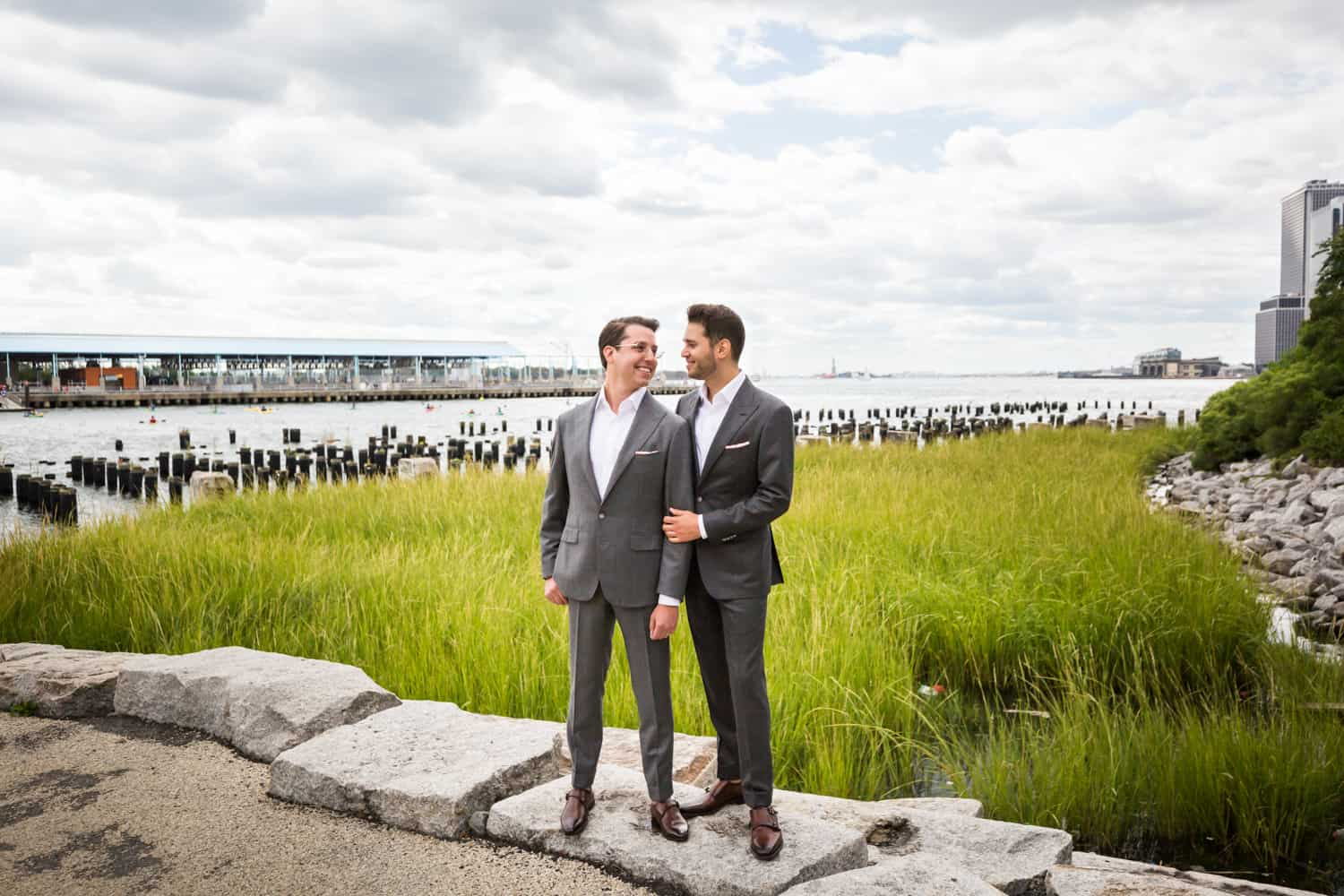 Greenpoint Loft wedding photos of two grooms in Brooklyn Bridge Park in front of Park Poles View