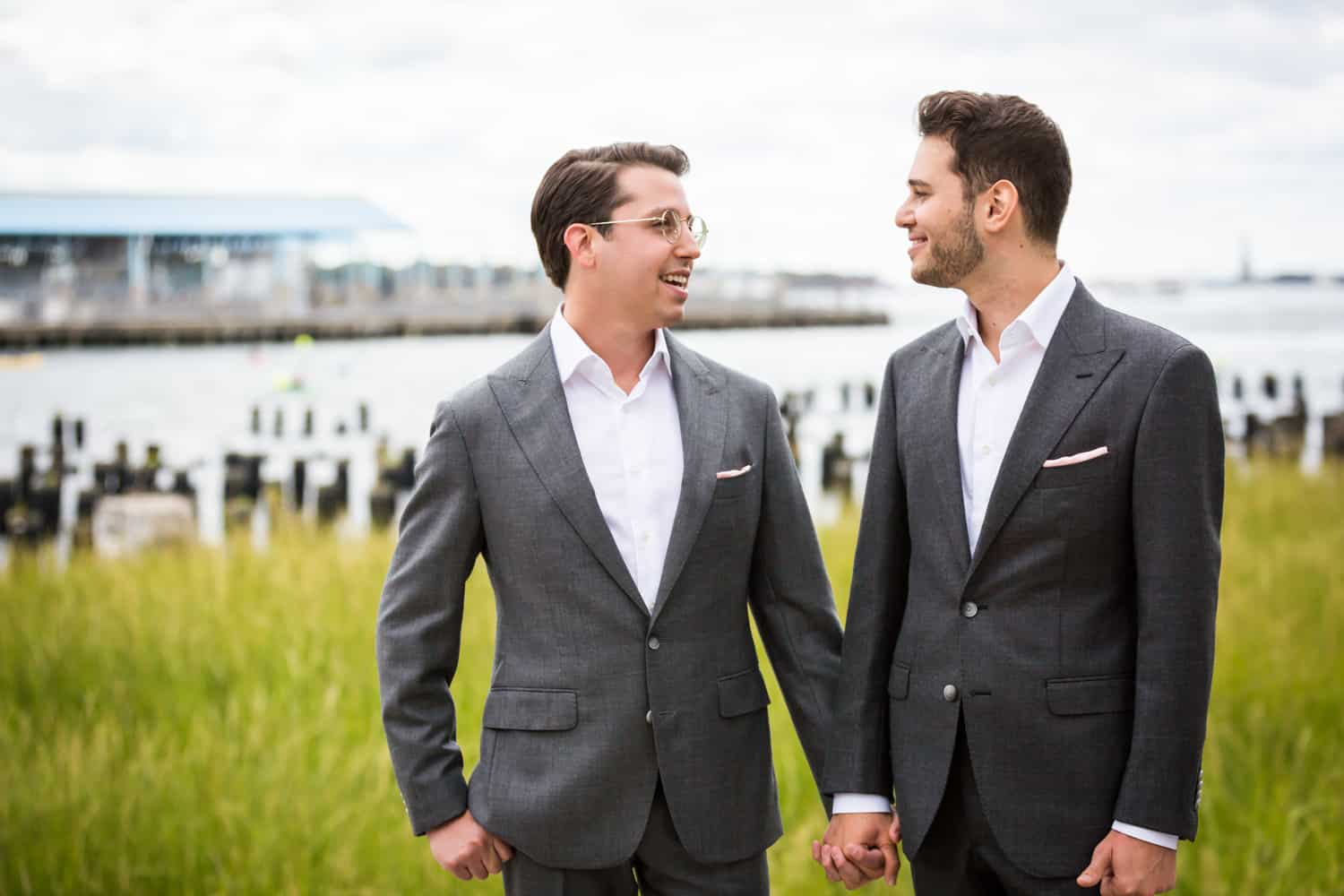 Greenpoint Loft wedding photos of two grooms holding hands in Brooklyn Bridge Park in front of Park Poles View