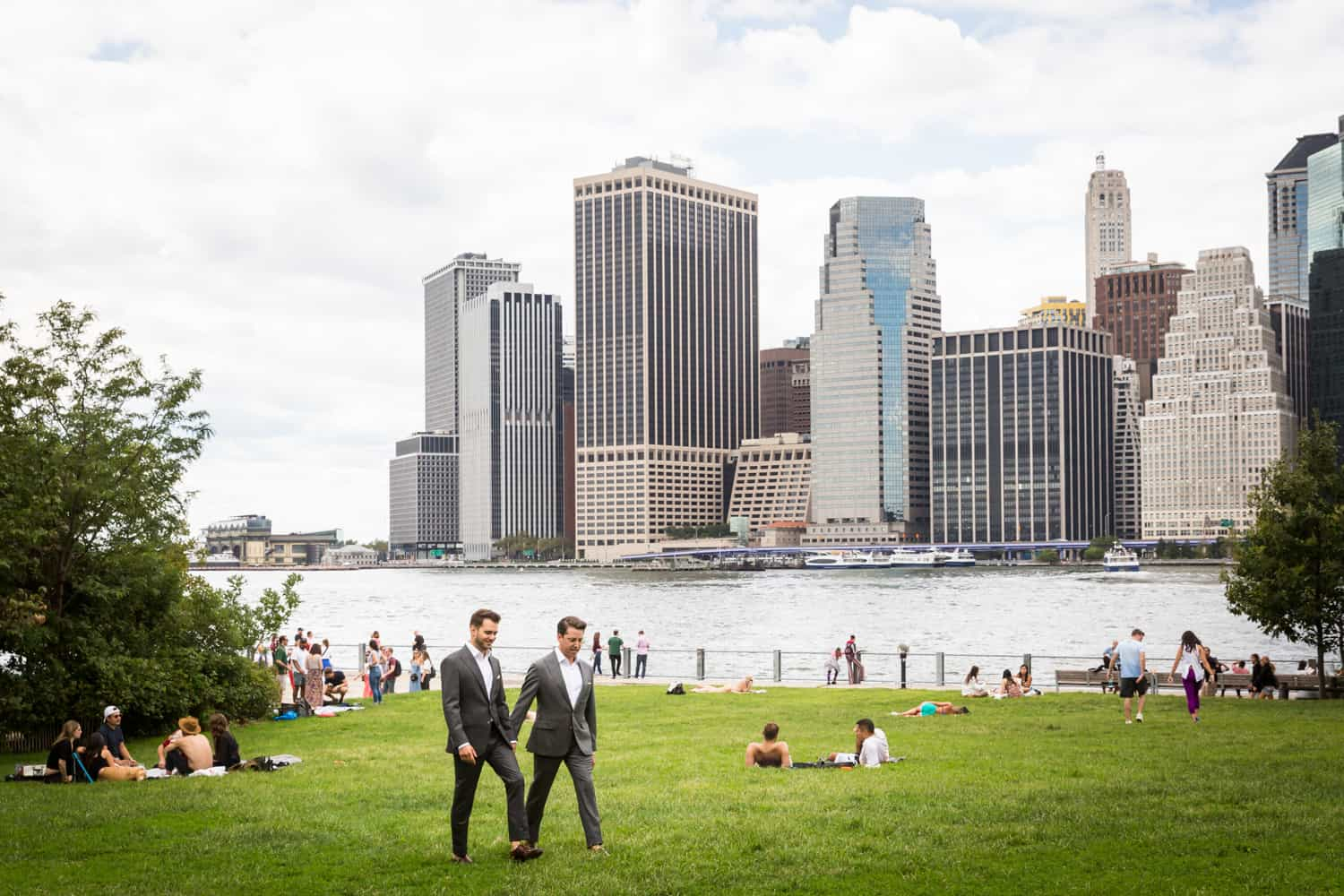 Greenpoint Loft wedding photos of two grooms walking across grass with NYC skyline in background