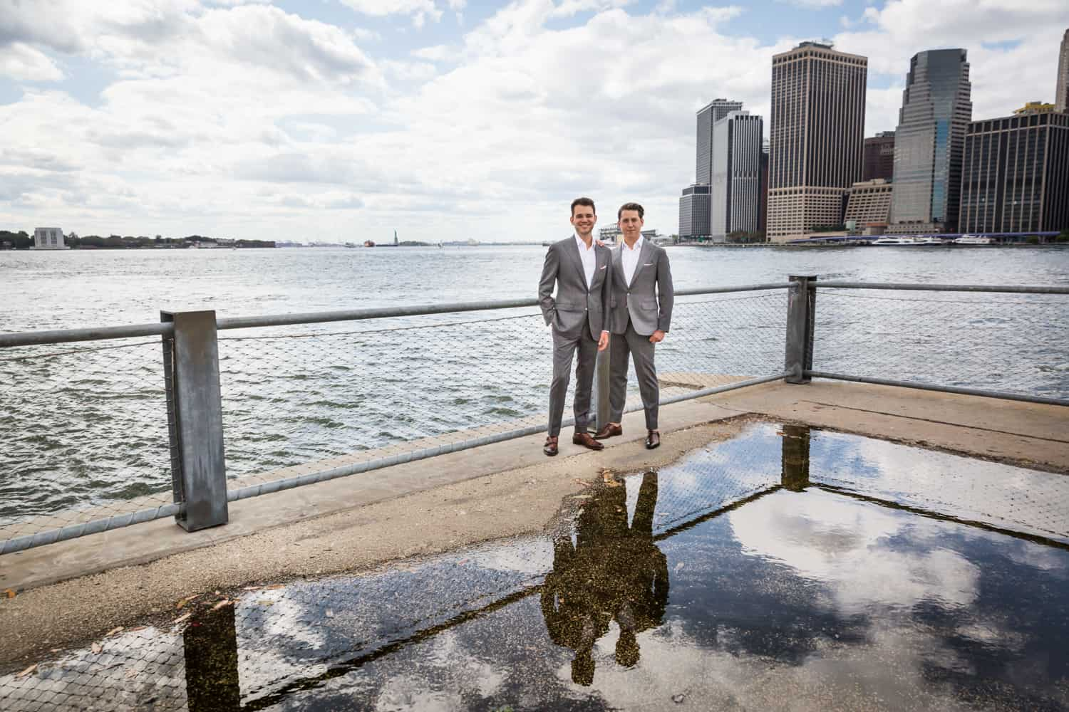 Greenpoint Loft wedding photos of two grooms at Brooklyn Bridge Park reflected in water puddle