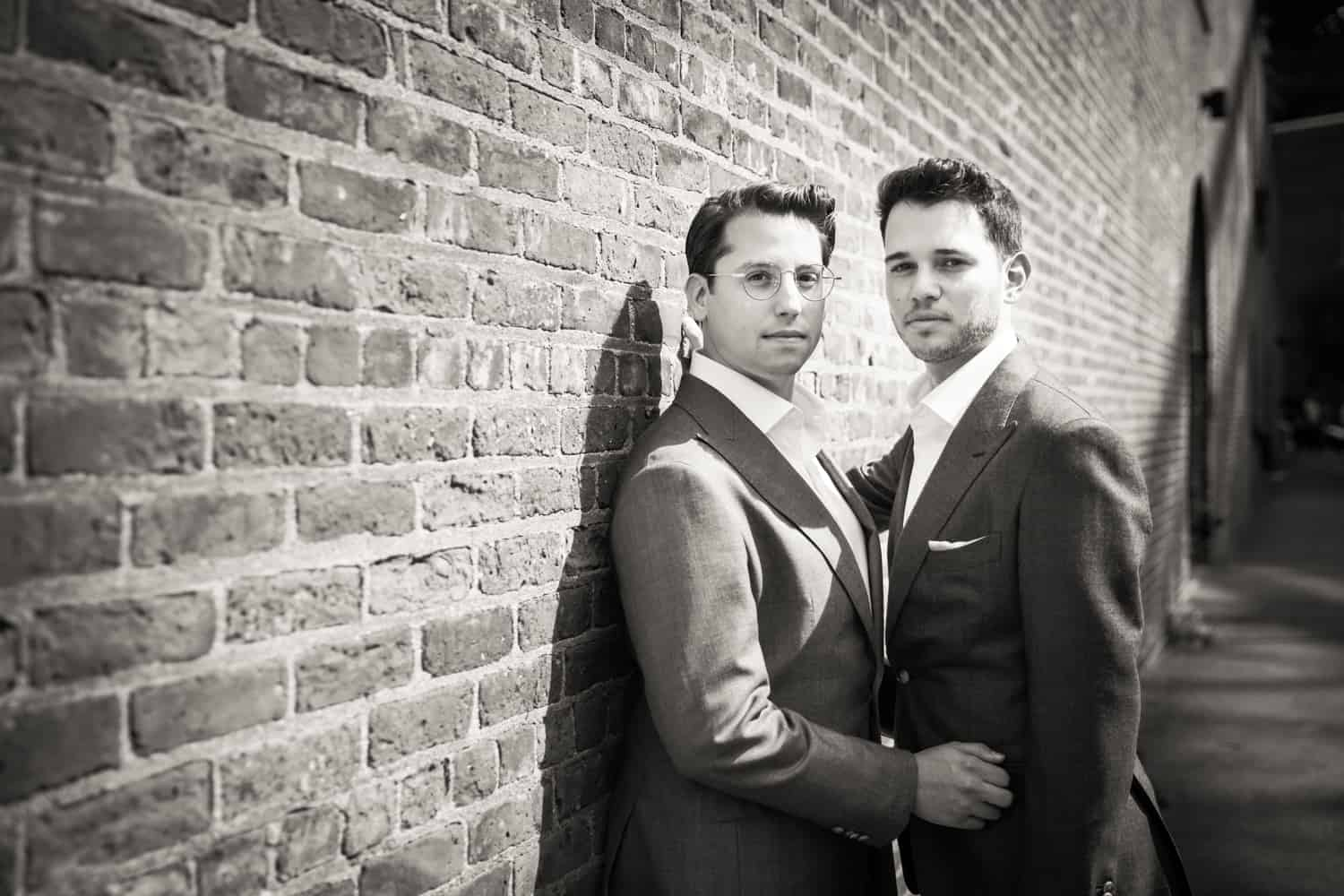 Black and white photo of two grooms leaning against brick wall