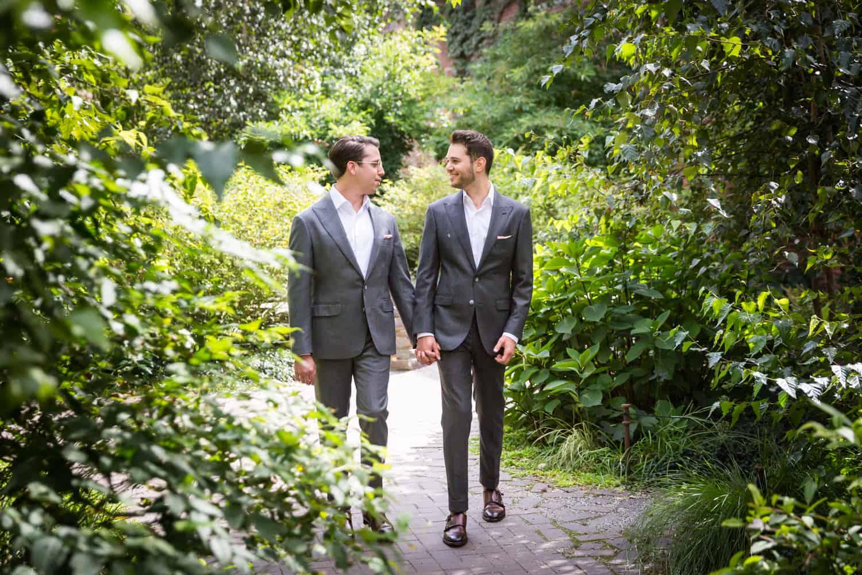 Greenpoint Loft wedding photos of two grooms walking through garden at St. Ann's Warehouse