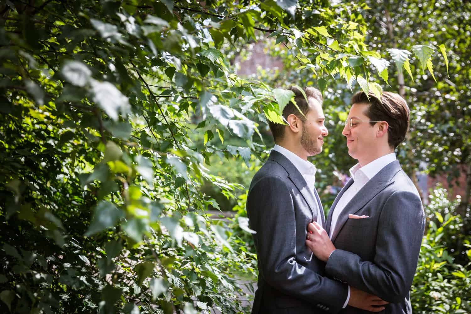 Greenpoint Loft wedding photos of two grooms in bushes at St. Ann's Warehouse
