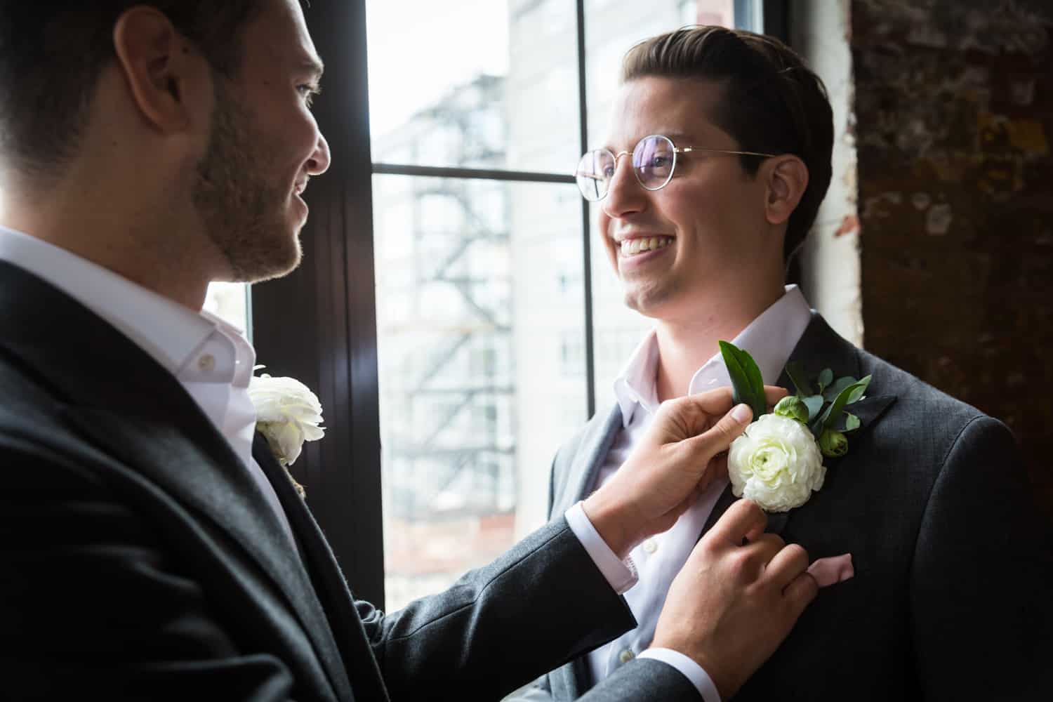 Greenpoint Loft wedding photos of groom helping other groom with his boutonniere
