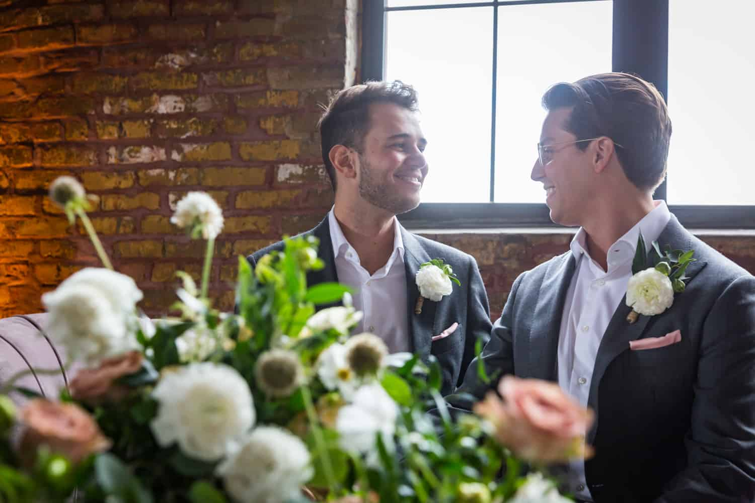 View over flowers of two grooms in front of window