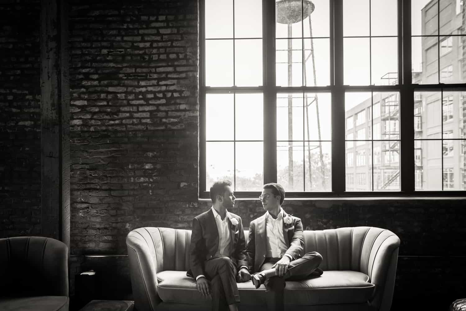 Black and white photo of two grooms sitting on couch under large window