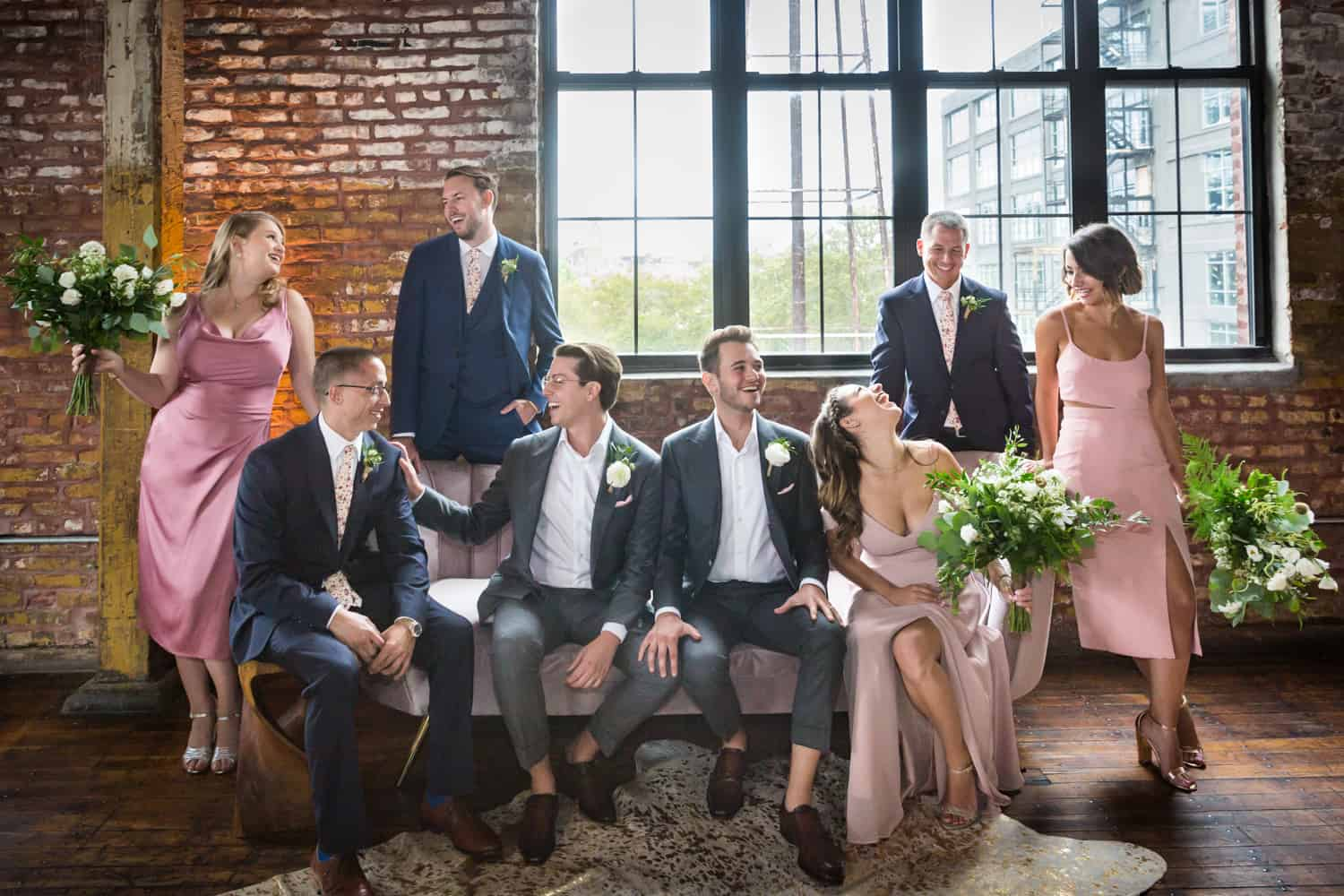 Greenpoint Loft wedding photos of bridal party lounging over couch with window in background
