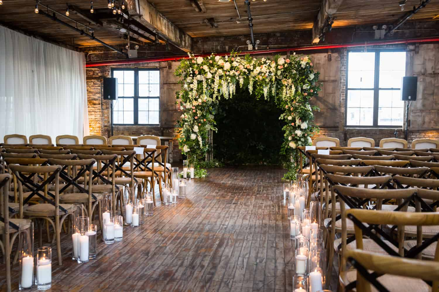 Wedding ceremony room at the Greenpoint Loft with blooming altarpiece and lit candles