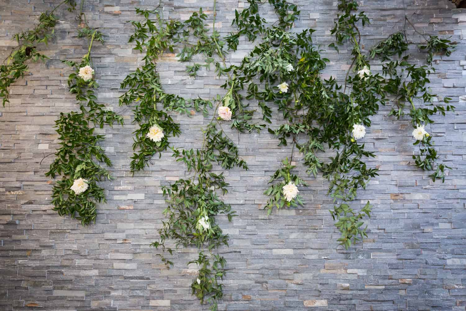 Grey brick wall covered with vines and flowers
